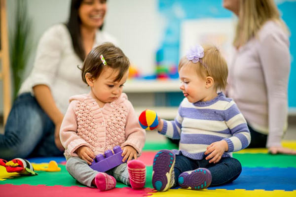 two young children playing together in a pre-school class